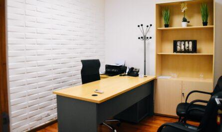 Dřevěný pracovní stůl umístěný v kanceláři.